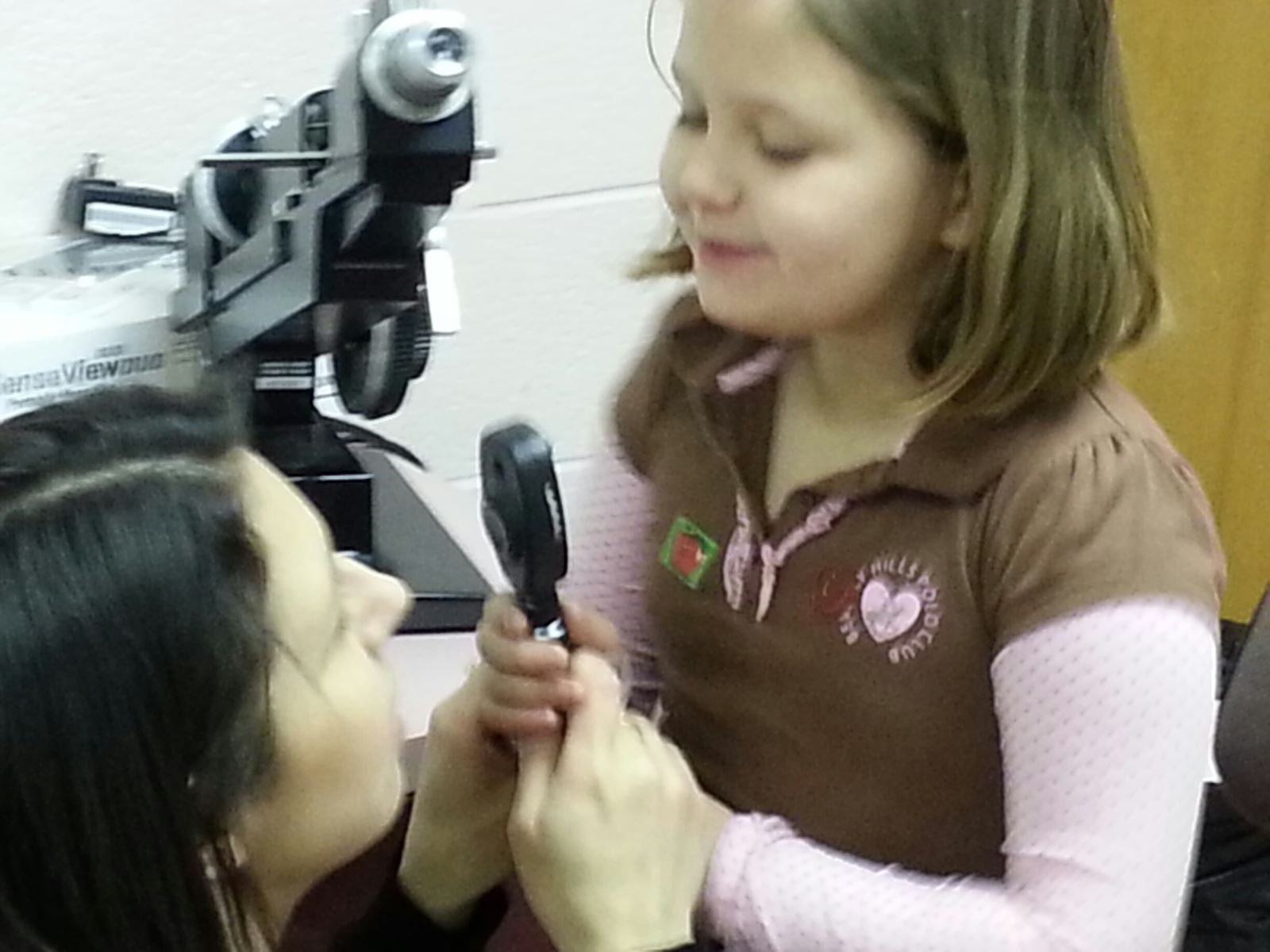 A female elementary student is holding an optical device with the opthalmologist during a low vision examination at KSB.