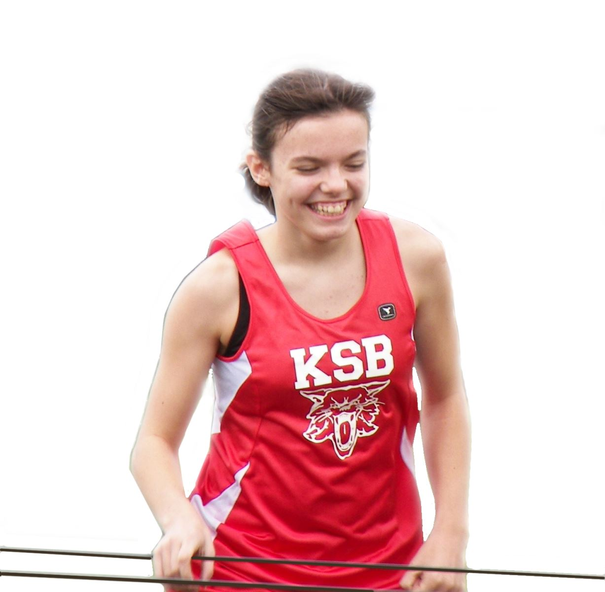 KSB varsity female athlete is holding on to a guide wire while running.  She is wearing a KSB wildcat jersey and has a broad smile on her face.