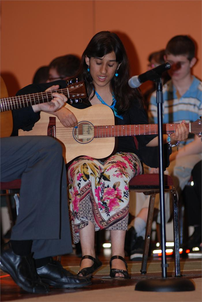 Female student giving guitar performance