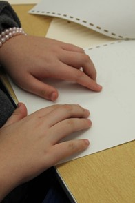 a child's hands on a page with braille