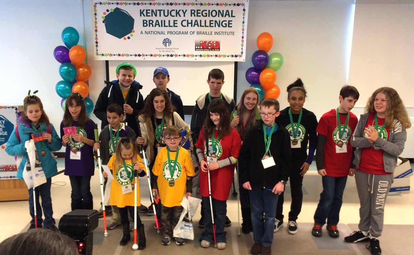Student 1st, 2nd. and 3rd. place winners of the Kentucky Regional Braille Challenge pose in front of signage and balloons at the American Printing House during the Awards Assembly.