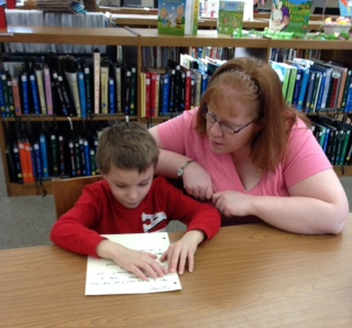 KSB teacher and an elementary male student are working at a table in the school library.  She is sitting to the right and is observing the student who is reading braille.