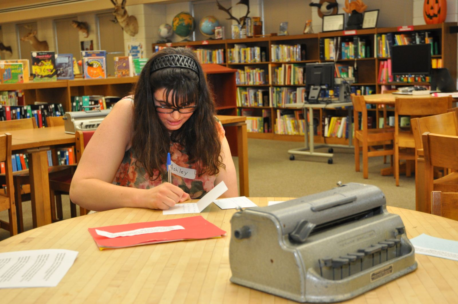 KSB high school student is reading a card in the school library.  She is seated at a table.  There is a braillewriter on the table.